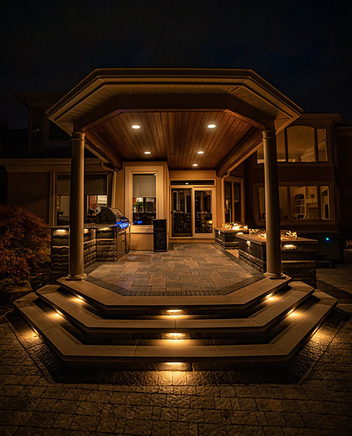 Dramatic outdoor patio area with concrete steps and elegant lighting in Westlake, Ohio